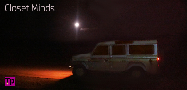 Silver Land Rover Defender on dirt road at night. Trying to visualize in our minds a moving vehicle.